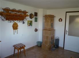 Společenská místnost se stylovým selským nábytkem a kachlovými kamny