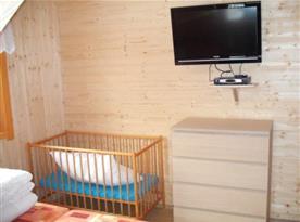Pokoj s televizí a dětskou postýlkou