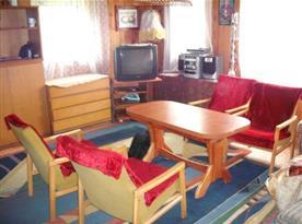 Společenská místnost s televizí, krbovými kamny a posezením