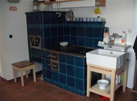 Kuchyně s kachlovou pecí, mikrovlnnou troubou, rychlovarnou konvicí, kávovarem a lednicí