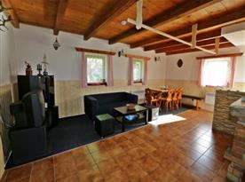 Společenská místnost s kachlovými kamny, krbem, sedačkou, televizí a jídelním koutem