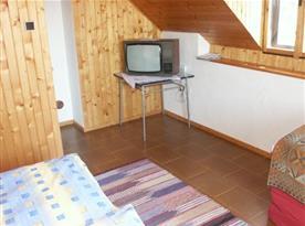 Podkrovní pokoj s lůžky a televizí