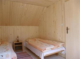 Pokoj s lůžky, nočními stolky a lampičkami v podkroví