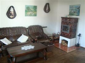 Společenská místnost se sedací soupravou a kachlovými kamny