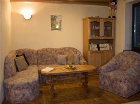 Společenská místnost se sedací soupravou a krbem