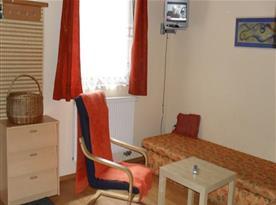 Obývací místnost s lůžkem, křeslem, stolkem a televizí