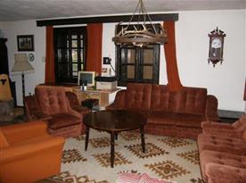 Společenská místnost  se sedací soupravou, křesli, televizorem a krbem