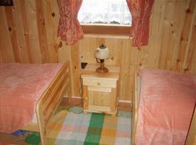 Pokoj s lůžky, nočním stolkem a lampičkami