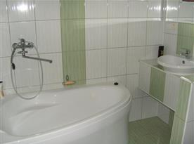 Koupelna v přízemí s vanou a umyvadlem