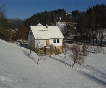 Pohled na chatu a blízké okolí v zimě