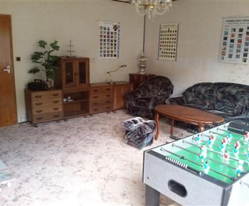 obývací pokoj se sedací soupravou, televizí a stolním fotbalem