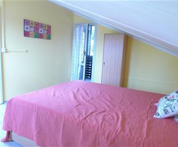 Ložnice s manželskou postelí a dvěma přistýlkami s posezením na balkóně