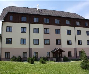 zadní vstup, apartmán v přízemí, dvě okna vlevo od vchodu