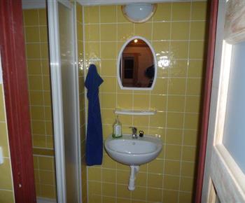 Sociální zařízení v přístavbě se sprchovým koutem, umyvadlem a zrcadlem