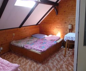 Podkrovní pokoj s lůžky, šachovým stolkem, koupelnou se sprchovým koutem a WC