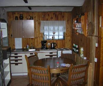 Kuchyně se sporákem, ledničkou, varnou konvicí a jídelním koutem