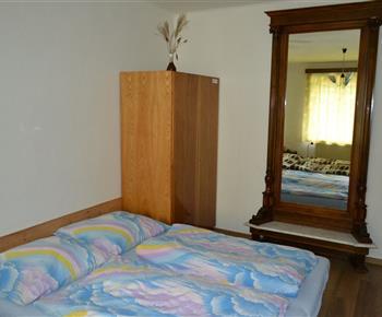 Část ložnice s velkým starožitným zrcadlem a skříní
