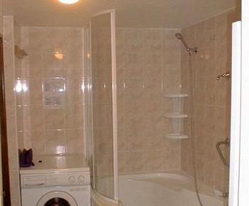 Koupelna s rohovou vanou a pračkou