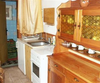 Menší kuchyně se sporákem, lednicí a varnou konvicí