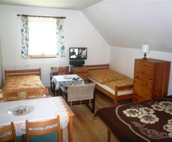 Podkrovní ložnice s lůžky a televizí