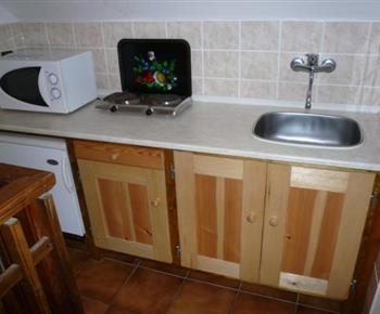 Menší kuchyně s plotýnkovým vařičem, ledničkou a mikrovlnou troubou
