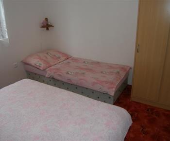 Ložnice v 3 lůžkové chatce s lůžky , skříní, lampičkou a televizí
