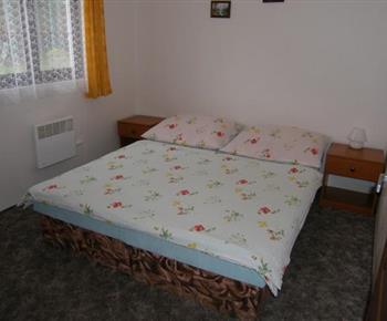 Ložnice ve 4 lůžkové chatce s lůžky, skříní, nočním stolkem a televizí