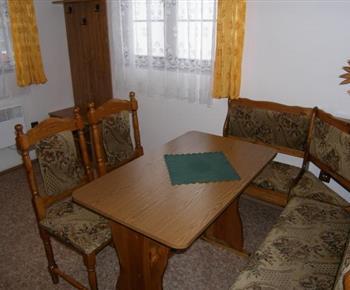 Jídelna ve 4 lůžkové chatce s rohovou lavicí, stolem a židlemi