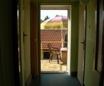 Pohled z chodby na venkovní posezení u apartmánu A