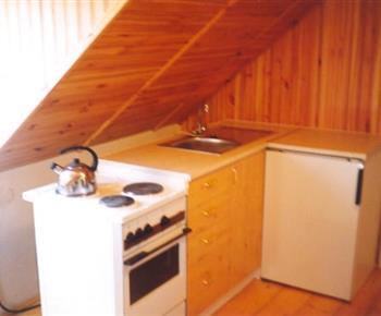 Menší kuchyňka v podkroví se sporákem a ledničkou