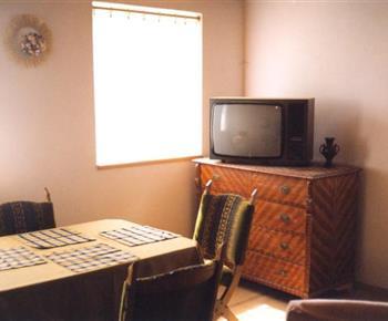 Obývací pokoj se sedací soupravou, televizí a komodou