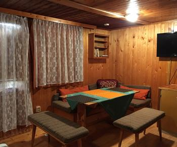 Obývací pokoj s rohovou sedačkou, stolkem, poličkou a televizí