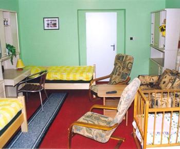 Pokoj s lůžky, skříňkou, dětskou postýlkou, sedací soupravou a televizí