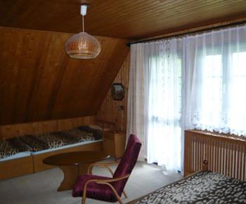 Podkrovní pokoj s lůžky, stolkem, křeslem a vstupem na balkón
