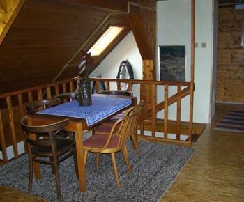 Podkrovní hala se stolem, židlemi a vstupem do pokojů