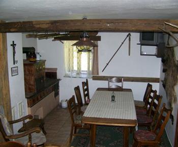 Jídelna má kachlová kamna, velký stůl, židle, křeslo a televizi