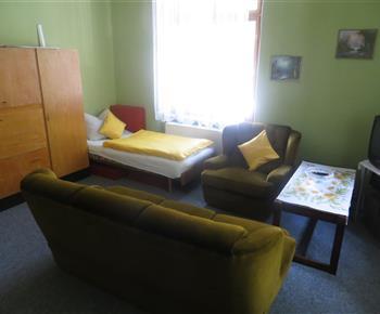 Levá část rohového pokoje s pohovkou a třetím lůžkem