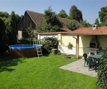 Bazén na zahradě objektu s posezením