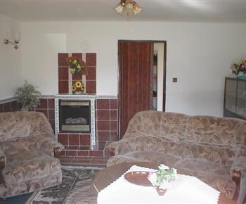 Obývací pokoj se sedací soupravou, stolkem, televizí a krbem