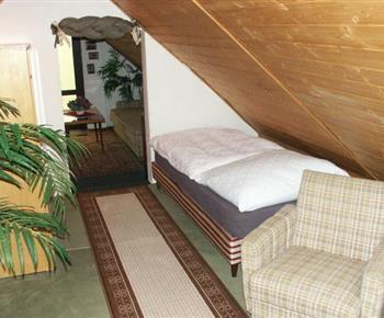 Podkrovní pokoj s lůžky, skříní a křesly
