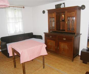 Ložnice D s pohovkou, stolem, příborníkem a zrcadlem