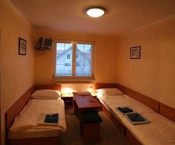 Pokoj s lůžky, stolkem, televizí, stolkem a lampičkou