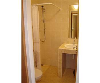 Koupelna s toaletou, sprchovým koutem, umývadlem a zrcadlem vlastní sociální zařízení