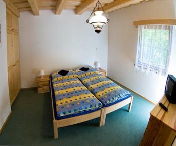 Ložnice s lůžky, nočními stolky, skříní a televizí