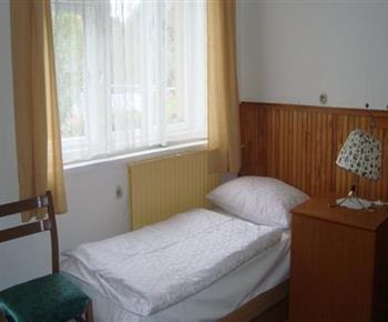Ložnice B s lůžkem, nočním stolkem a lampičkou