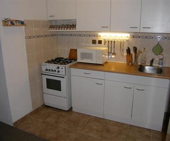Kuchyň se sporákem, lednicí, mikrovlnou troubou a rychlovaranou konvicí