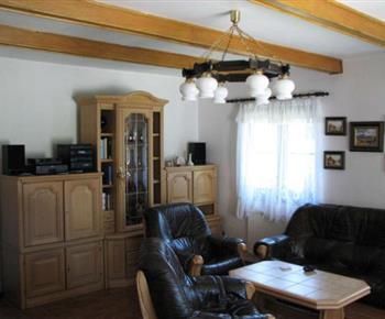Obývací pokoj s koženou sedací soupravou a televizí