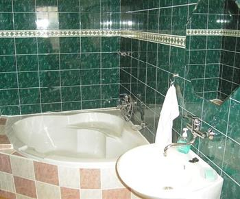 Rohová vana, umývadlo a zrcadlo v koupelně ve vile A