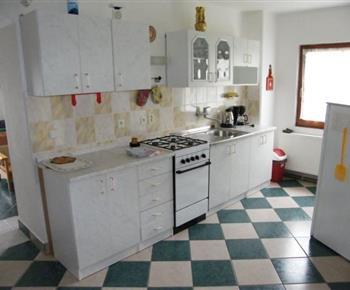 Kuchyně ve vile C vybavená plynovým sporákem s troubou, rychlovarnou konvicí, kávovarem a lednicí