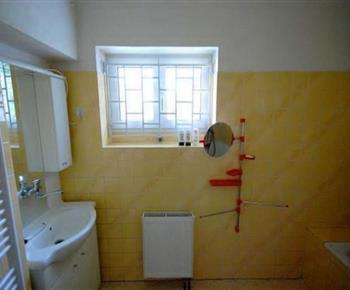Koupelna v přízemí s vanou, umývadlem a zrcadlem